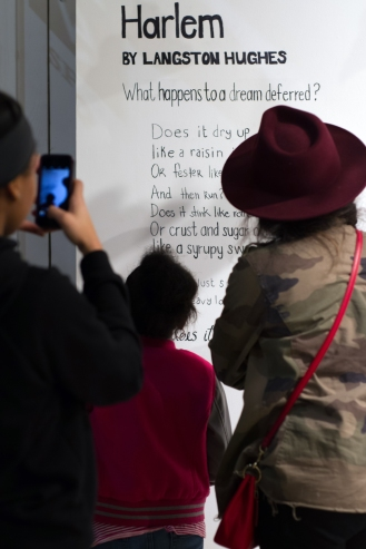 Opening night - visitors reading Langston Hughes' poem and the inspiration behind the project.