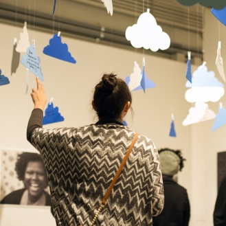 Opening night - a woman reading through some of the community dreams on clouds.